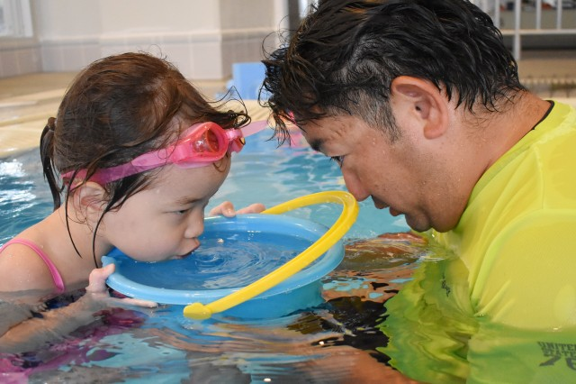 """Naoyuki """"Pedro"""" Ishikawa, right, swim instructor, helps Olivia Freyer, 5, learn how to blow bubbles in the water during a pre-K swim class at the Yano Fitness Center, Camp Zama, Japan, Aug. 20."""
