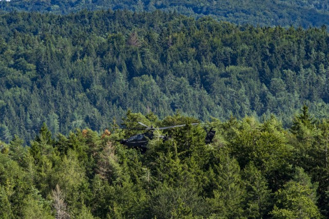 An Army AH-64 Apache Attack Helicopter belonging to the 1st Squadron, 6th Cavalry Regiment, 1st Combat Aviation Brigade, 1st Infantry Division, conceals among the treetops during a simulated attack mission as part of Combined Resolve XII on a range at Hohenfels Training Area, Germany, Aug. 16, 2019. Combined Resolve is a biannual U.S. Army Europe and 7th Army Training Command-led exercise intended to evaluate and certify the readiness and interoperability of US forces mobilized to Europe in support of Atlantic Resolve. (U.S. Army photo by Sgt. Jeremiah Woods)