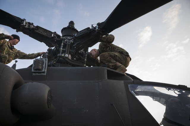 U.S. Army Soldiers with 1st Combat Aviation Brigade, 1st Infantry Division, inspect an AH-64 Apache Attack Helicopter, following a successful flight during the culminating force on force exercise of Combined Resolve XII at the Joint Multinational Readiness Center in Hohenfels, Germany Aug. 16, 2019. Combined Resolve is a biannual U.S. Army Europe and 7th Army Training Command-led exercise intended to evaluate and certify the readiness and interoperability of US forces mobilized to Europe in support of Atlantic Resolve.  (U.S. Army photo by Sgt. Thomas Mort)