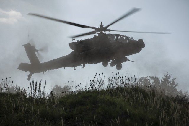 An AH-64 Apache Attack Helicopter with the 1st Squadron, 6th Cavalry Regiment, 1st Combat Aviation Brigade, 1st Infantry Division hovers in a field during a simulated attack mission, as part of the culminating force on force exercise of Combined Resolve XII at the Joint Multinational Readiness Center in Hohenfels, Germany Aug. 22, 2019. Combined Resolve is a biannual U.S. Army Europe and 7th Army Training Command-led exercise intended to evaluate and certify the readiness and interoperability of US forces mobilized to Europe in support of Atlantic Resolve.  (U.S. Army photo by Sgt. Thomas Mort)