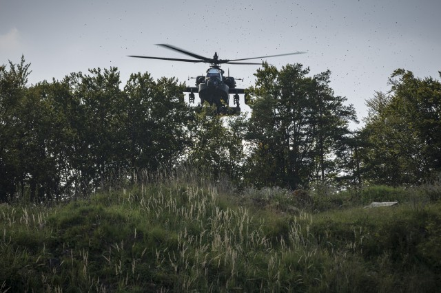 An AH-64 Apache Attack Helicopter with the 1st Squadron, 6th Cavalry Regiment, 1st Combat Aviation Brigade, 1st Infantry Division hovers just over the tree line to mask itself against ground observation, as part of the culminating force on force exercise of Combined Resolve XII at the Joint Multinational Readiness Center in Hohenfels, Germany Aug. 22, 2019. Combined Resolve is a biannual U.S. Army Europe and 7th Army Training Command-led exercise intended to evaluate and certify the readiness and interoperability of US forces mobilized to Europe in support of Atlantic Resolve.  (U.S. Army photo by Sgt. Thomas Mort)