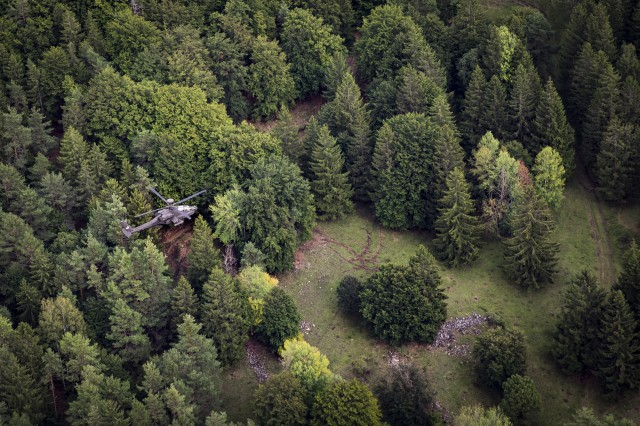 An Army AH-64 Apache Attack Helicopter belonging to the 1st Squadron, 6th Cavalry Regiment, 1st Combat Aviation Brigade, 1st Infantry Division, patrols the forest during a simulated mission as part of Combined Resolve XII on a range at Hohenfels Training Area, Germany, Aug. 19, 2019. Combined Resolve is a biannual U.S. Army Europe and 7th Army Training Command-led exercise intended to evaluate and certify the readiness and interoperability of US forces mobilized to Europe in support of Atlantic Resolve. (U.S. Army photo by Sgt. Jeremiah Woods)