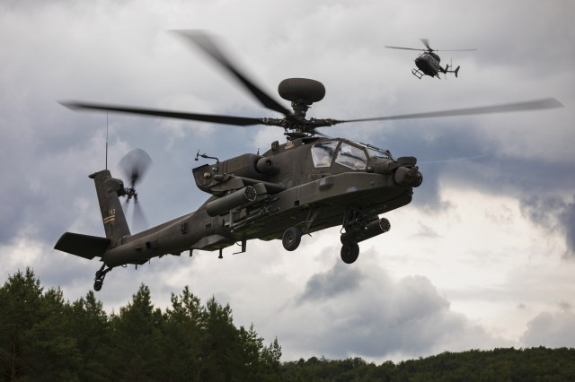 An AH-64 Apache Helicopter with 1st Combat Aviation Brigade, 1st Infantry Division, flies out into the box as an Observer Controller (OC) helicopter trails behind, during a simulated attack mission, as part of the culminating force on force exercise of Combined Resolve XII at the Joint Multinational Readiness Center in Hohenfels, Germany Aug. 19, 2019. Combined Resolve is a biannual U.S. Army Europe and 7th Army Training Command-led exercise intended to evaluate and certify the readiness and interoperability of US forces mobilized to Europe in support of Atlantic Resolve.  (U.S. Army photo by Sgt. Thomas Mort)