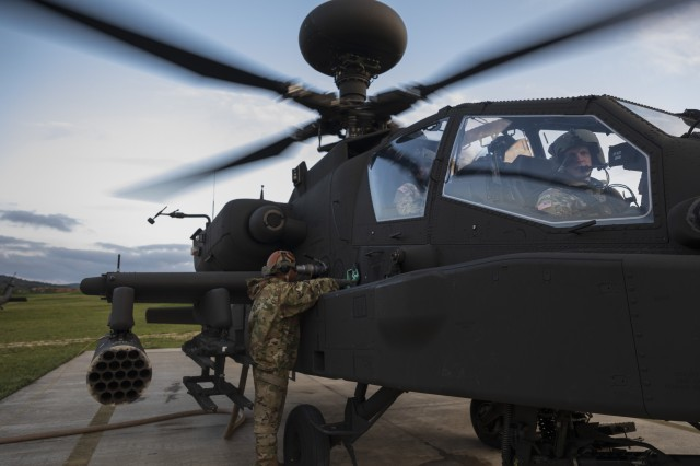 A U.S. Army Soldier with the 1st Combat Aviation Brigade, 1st Infantry Division, refuels an AH-64 Apache Attack Helicopter with the 1st CAB prior to a simulated attack mission during the culminating force on force exercise of Combined Resolve XII at the Joint Multinational Readiness Center in Hohenfels, Germany Aug. 16, 2019. Combined Resolve is a biannual U.S. Army Europe and 7th Army Training Command-led exercise intended to evaluate and certify the readiness and interoperability of US forces mobilized to Europe in support of Atlantic Resolve.  (U.S. Army photo by Sgt. Thomas Mort)