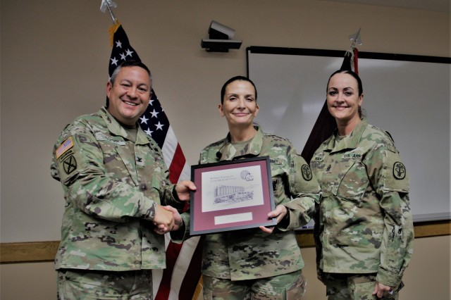 Col. Michael S. Oshiki, commander of William Beaumont Army Medical Center, and Command Sgt. Maj. Janell Ray (right) present Sgt. Maj. Tammy Bosier (middle), senior enlisted advisor to the deputy commander of WBAMC, a gift for speaking at the WBAMC Women's Equality Day Observance, August 15, 2019, in the clinical assembly room of the main hospital.