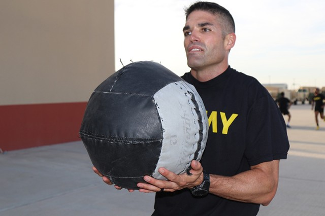 Cox throws medicine balls during a morning physical training session in the 22nd Chemical Battalion holistic health and fitness training facility to practice for the Army Combat Fitness Test.