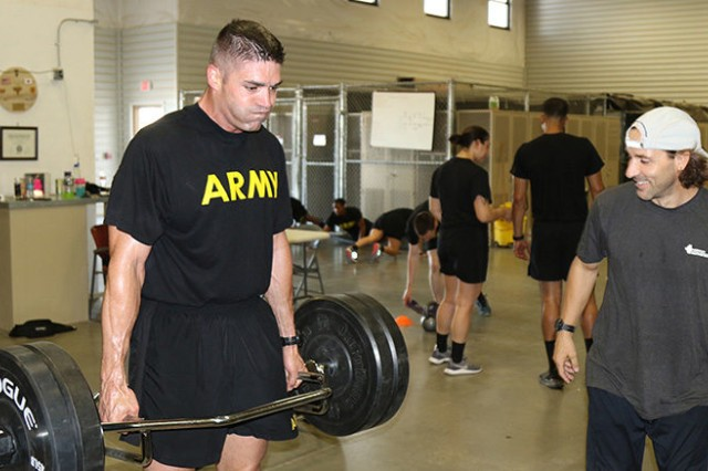 Major Timothy Cox lifts weights during physical training while the lead strength coach of 22nd Chemical Battalion, Mike Edwards, supervises him for proper form in the holistic health and fitness training facility.