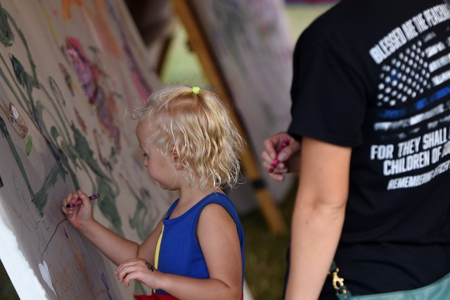 Mom watches as 5-year-old Riley Gilliam of Fort Knox paints pictures and writes her name on an easel at the Party in the Park event Aug. 23, 2019.