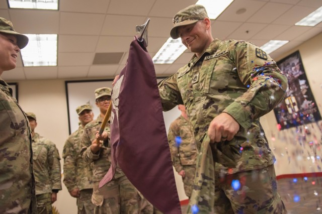 The 126th FRST's Commander Maj. Elizabeth Wheeler and Detachment Sergeant Sgt. 1st Class Nathaniel Durand unfurl their unit guidon from its casing as red, white and blue confetti flies out to the delight of those in attendance.  The team of 14 commissioned and noncommissioned officers from 126th FRST returned from a nine month deployment in Syria in support of Operation Inherent Resolve Aug. 23. (U.S. Army photo by Sgt. 1st Class Kelvin Ringold)