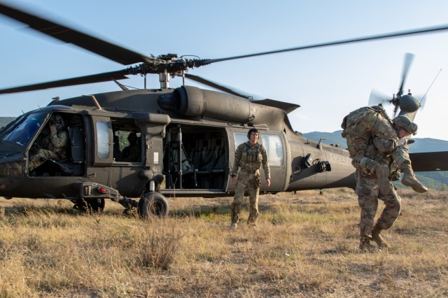 A U.S. Army Soldier from the 3rd Assault Helicopter Battalion, 1st Aviation Regiment carries a crew chief from a UH-60 Black Hawk helicopter as part of personnel recovery training in Novo Selo Training Area, Bulgaria, August 26th, 2019. After touching down in an unknown location, the Soldiers had to use their basic flight gear and skills they learned in the classroom to make it home during this realistic overnight training. (U.S. Army Photo by Pfc. Andrew Wash)
