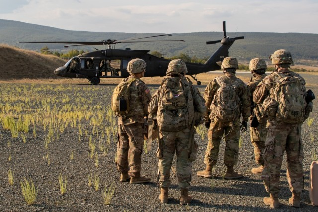 U.S. Army Soldiers from the 3rd Assault Helicopter Battalion, 1st Aviation Regiment await transport to an unknown training location in Novo Selo Training Area, Bulgaria, August 26th, 2019, as part of a culminating event during personnel recovery training.  The personnel recovery lanes incorporated realistic hands-on training in land navigation, survival, tactical communications and first aid. (U.S. Army photo by Pfc. Andrew Wash, 5th Mobile Public Affairs Detachment)
