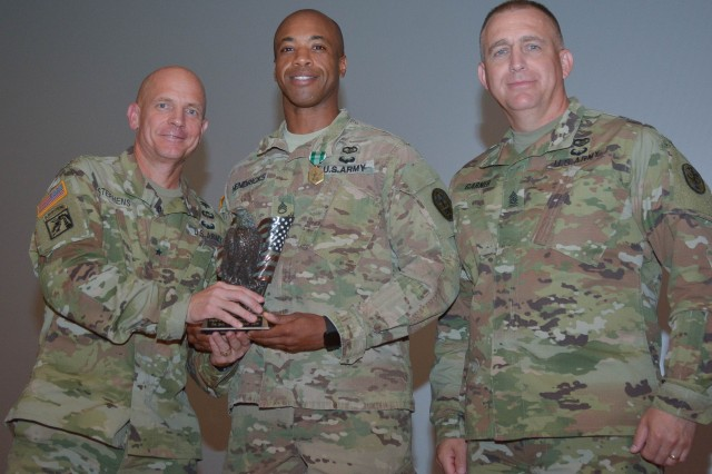 Staff Sgt. Gary Hendricks, assigned to Grafenwoehr Army Health Clinic, poses for a photo with his trophy after being awarded 'Best Medic' for Regional Health Command Europe. Brig. Gen. Ronald Stephens, commanding general for RHCE, and Command Sgt. Maj. Todd Garner, RHCE's command sergeant major, presented Hendricks with his trophy.