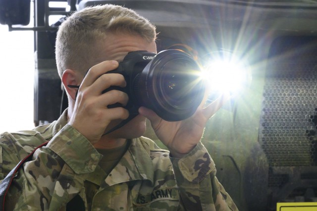 U.S. Army Reserve Spc. Tucker White, a broadcast specialist with the 350th Public Affairs Detachment in Indianapolis, focuses his camera to take a photo during a Joint Light Tactical Vehicle maintenance session as part of the 46 Sierra conversion training, Fort McCoy, Wisconsin, Aug. 13, 2019. Soldiers practiced with Digital Single Lens Reflex cameras, the new standard issue to their kit, in order to increase their proficiency. (U.S. Army Reserve photo by Spc. Maximilian Huth)