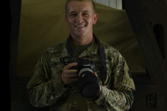 U.S. Army Reserve Soldier Spc. Tucker White, a broadcast specialist at the 350th Public Affairs Detachment headquartered in Indianapolis, poses with his camera during the 46 Sierra Conversion Training in Fort McCoy, Wisconsin, Aug. 12, 2019. White learned photography and news writing in order to become a mass communication specialist as part of a military occupational specialty merge. (U.S. Army Reserve photo by Spc. Maximilian Huth)