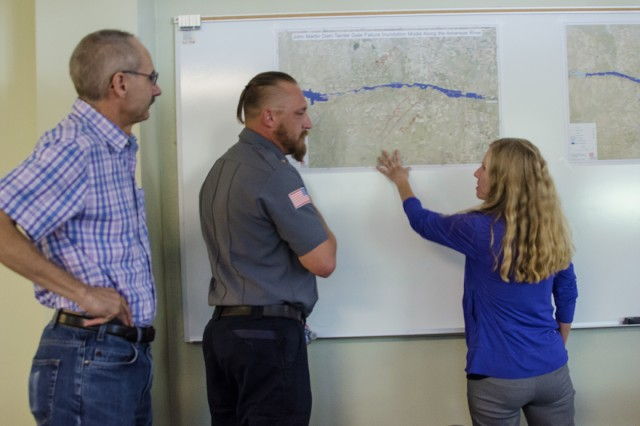 Mark Yuska, chief, Operations (left), and Amy Louise, Arkansas River Basin manager, both USACE-Albuquerque District, discuss inundation with Jeremy Burkhart, chief and emergency manager, Lamar Fire Department, during the exercise at Lamar Community College Aug. 15, 2019.