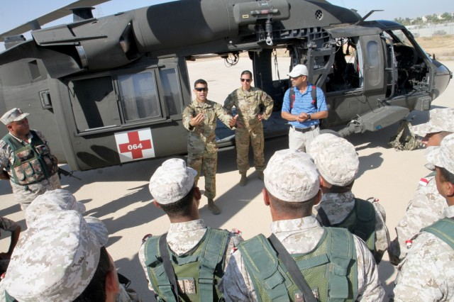 U.S. Army Sgt. Ignacio Aparicio, center, crew chief, Golf Company, 5th Battalion, 159th Aviation Regiment, talks to members of Jordan Armed Forces' 7th Mechanized Infantry Battalion about hand signals and casualty loading procedures during medical evacuation training in preparation for exercise Eager Lion 2019, Aug. 21, 2019. This multinational exercise is U.S. Central Command's premier exercise in the Levant region and is a major training event that provides U.S. forces, Jordan Armed Forces and 28 other participating nations the opportunity to improve their collective ability to plan and operate in a coalition-type environment.