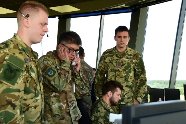 U.S. Air Force Lt. Col. Allen Kao, a public health officer assigned to the 179th Medical Group, answers the phone and works alongside his Hungarian counterparts during a simulated in-flight emergency response exercise Aug. 1, 2019, at Pápa Air Base, Hungary. The simulation was a part of a three-weeklong intermediate airfield management course that an Ohio National Guard mobile training team led for its Hungarian partners. Ohio and Hungary have been paired through the Department of Defense State Partnership Program since 1993.