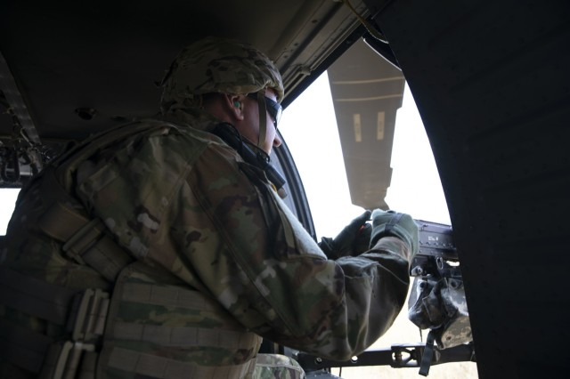 A Soldier with the 3rd Assault Helicopter Battalion, 1st Aviation Regiment, fires an M240H machine gun from a stationary UH-60 Black Hawk helicopter during a prerequisite familiarization range August 27th, 2019, at Novo Selo Training Area, Bulgaria. The training was part of an aerial gunnery qualification range that included day and night fire. (U.S. Army photo by Sgt. Erica Earl)
