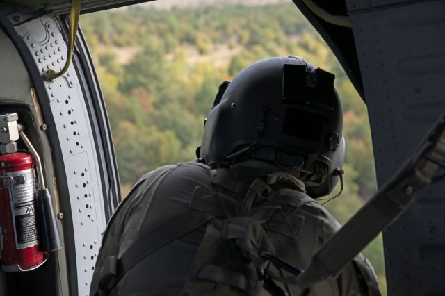 A U.S. Army Soldier with the 3rd Assault Helicopter Battalion, 1st Aviation Regiment looks out from a UH-60 Black Hawk helicopter on the way to the personnel recovery lane site August 27th, 2019, at Novo Selo Training Area, Bulgaria. The personnel recovery exercise was an overnight training event in which Soldiers practiced land navigation, tactical communication, survival techniques and first aid. (U.S. Army photo by Sgt. Erica Earl)