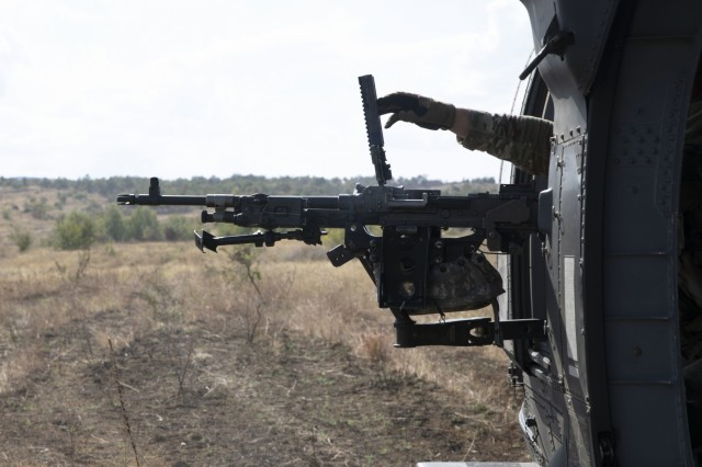 A U.S. Army Soldier with the 3rd Assault Helicopter Battalion, 1st Aviation Regiment, reaches out from a UH-60 Black Hawk helicopter to clear an M240H machine gun during a qualification range August 27th, 2019, at Novo Selo Training Area, Bulgaria. Twenty crew chiefs and four pilots in command participated in the aerial gunnery qualification range. (U.S. Army photo by Sgt. Erica Earl)