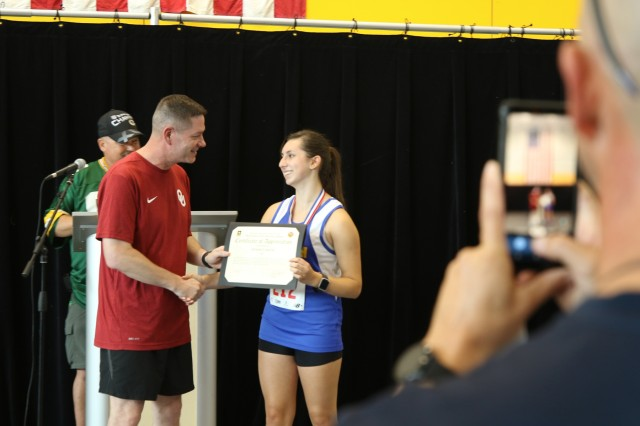 Col. Steven M. Pierce, Garrison Commander, U.S. Army Garrison Ansbach, awards Adriana Cadavid for her volunteer hours at the Ansbach Terrace Playhouse, August 24, 2019, Katterbach, Germany. Cadavid was one of many young volunteers recognized at the 2019 U.S. Army Garrison Ansbach, Sportin' The Home Team Community Showcase.