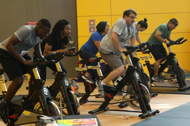 Mike Cercone, Indoor Cycling instructor, seen front and center, leads a demonstration of his rigorous cycling class at 2019 U.S. Army Garrison Ansbach, Sportin' The Home Team Community Showcase, August 24, 2019, Katterbach, Germany. Indoor Cycling is one of the many classes available to Soldiers and their families at the Katterbach Fitness Center.