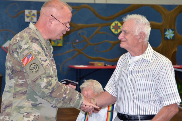 Major General Ray Shields, the Adjutant General of New York, presents the military challenge coin to Air Force Korean War veteran Merton W. Houghton during an awards ceremony at the former New York State Armory in Hoosick Falls, N.Y. on Wednesday, August 28, 2019. Shields honored ten local veterans with New York state awards recognizing their military service during the event.