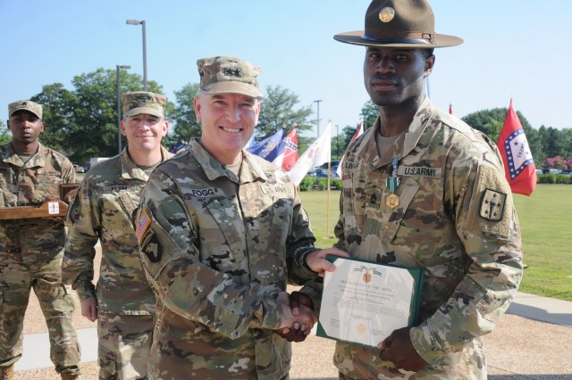 Sgt. 1st Class Frank Dunbar proudly accepts an Army Commendation Medal presented by Maj. Gen. Rodney D. Fogg, CASCOM and Fort Lee commanding general, and Command Sgt. Maj. Michael Perry III, CASCOM CSM, during the Drill Sergeant of the Year Competition awards ceremony July 3 at Seay Field. The Tango Company, 266th Quartermaster Battalion NCO emerged as the winner of the four-day event that concluded earlier that day with a pre-dawn 12-mile ruck march.