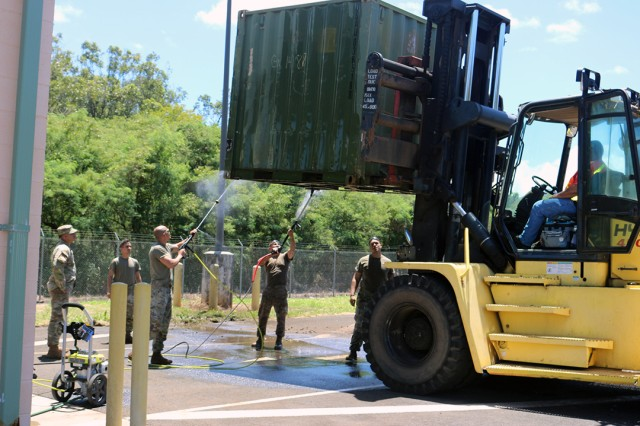25th ID Soldiers spray wash and scrub the bottoms of containers at the Multifunctional Deployment Facility on July 24 so they will pass agricultural inspection for shipment.