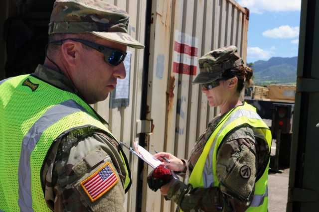 Sgts. 1st Class Amanda Reilly and Dennis Bordelon, 1192nd DDST from New Orleans, Louisiana, inspect the contents of containers at the 25th CAB motor pool on July 24.