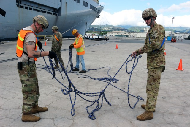 25th Infantry Division Soldiers and FLC-Pearl Harbor personnel straighten tag lines before lifting a helicopter onto the USNS Brittin during upload operations at Pearl Harbor on Aug 10.