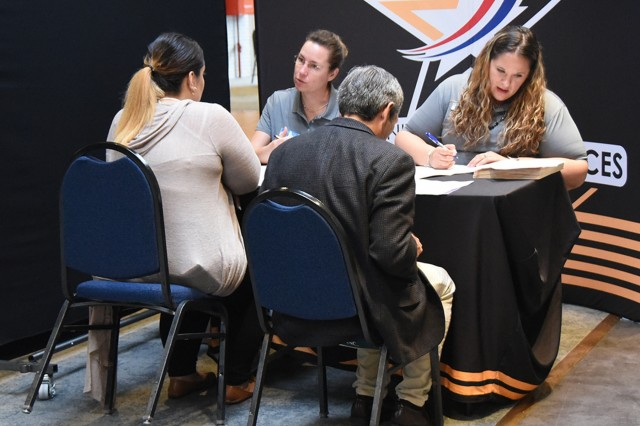 Julia Merrick-Rocha (back left) and Jessica Ross (back right), Child and Youth Services employees, review applications and resumes during CYS's on-the-spot hiring sessions during the Benelux Employment, Volunteer and Career Expo Sept. 6, 2018, on SHAPE, Belgium. CYS and other organizations accepted resumes and interviewed potential candidates during the event.