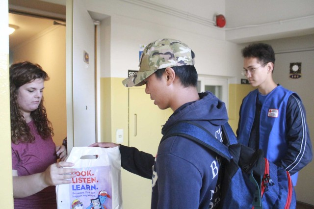 Youth volunteers from the American Red Cross and Boy Scout Venture Crew 73 assist the USAG Daegu fire department in canvassing Army family housing during the 2018 Fire Prevention Week.