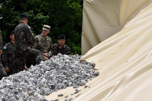 Blue Grass Army Depot Commander, Col. Joseph R. Kurz, discusses the benefits of igloo tarp covers with Republic of Korea officers during their visit to BGAD in May 2019.