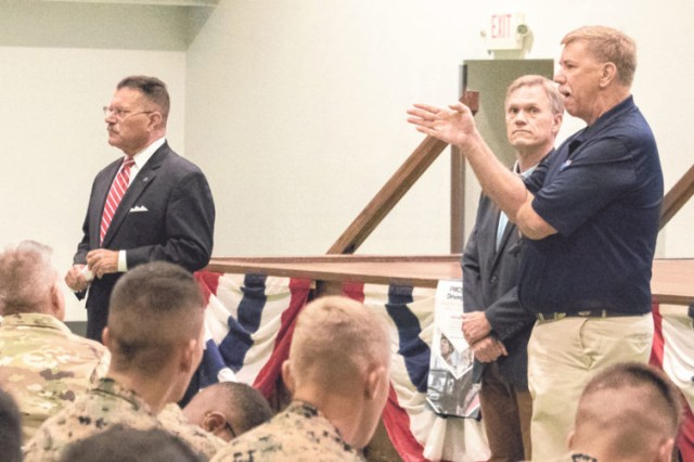 From left, Raymond Martinez, Wiley Deck and Selden Fritschner, all of FMSCA, address questions about commercial license certification with service members in Nutter Field House Tuesday.