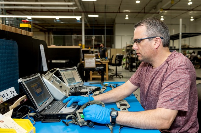 Tobyhanna Army Depot electronics mechanic Brian Brown updates software after employees overhaul an individual weapon system harness.
