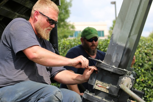 "John Buggy (left) and Shane Kimbrough, mechanics from Redstone Arsenal's Logistics Readiness Center, troubleshoot a ""frozen"" actuator on AMCOM's display Patriot missile launcher. The launcher was partially disassembled and transported to Oklahoma to represent air defense artillery units and soldiers stationed at Fort Sill."
