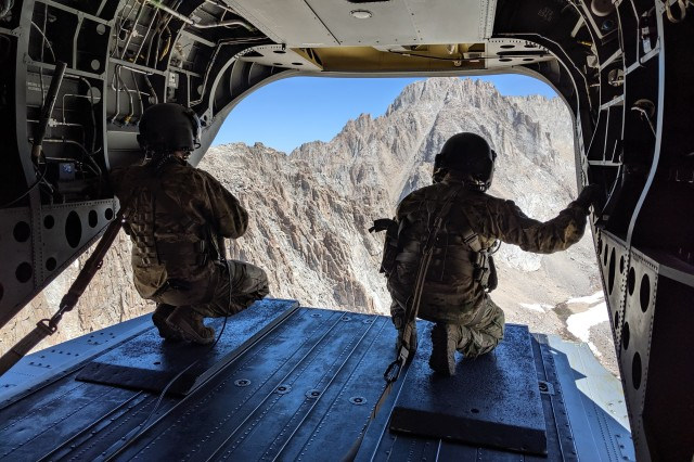 A pair of U.S. Army soldiers assigned to B Company, 1st Battalion, 126th Aviation Regiment, California Army National Guard, look out from their CH-47F Chinook helicopter while flying on a rescue mission, Aug. 25, 2019, on Mount Whitney in Inyo County, California. At 14,500 feet, the mountain is the tallest peak in the contiguous United States. Cal Guard assists local, state and federal agencies during search and rescue missions and domestic disaster response efforts.