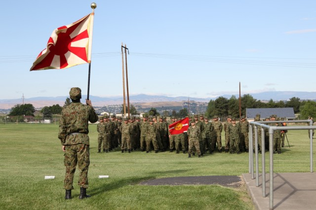 The flag of the Japan Ground Self-Defense Force flies in front of the formation during the opening ceremony of Rising Thunder 2019, Aug 30, 2019 at Yakima Training Center, Washington. Rising Thunder 2019 is an annual exercise joining the U.S. Army and the Japan Ground Self Defense Force (JGSDF) and is part of Pacific Pathways 19-3. Rising Thunder 2019 is also a United States Army Pacific-sponsored capstone event featuring U.S. Army units from the 7th Infantry Division and the Illinois Army National Guard's 33rd Infantry Brigade Combat Team and 108th Sustainment Brigade. The exercise includes of company/platoon unilateral and bilateral training events in two phases, culminating with a bilateral live-fire exercise. (Photo by Army Reserve Sgt. Camacho Roberts)