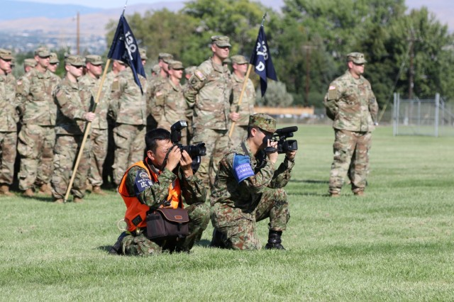 Public affairs specialists from the Japan Ground Self-Defense Force capture images from the Rising Thunder 19 opening ceremony. The ceremony took place at Yakima Training Center, Washington, Aug. 30, 2019. Rising Thunder 2019 is an annual exercise joining the U.S. Army and the Japan Ground Self Defense Force (JGSDF) and is part of Pacific Pathways 19-3. Rising Thunder 2019 is also a United States Army Pacific-sponsored capstone event featuring U.S. Army units from the 7th Infantry Division and the Illinois Army National Guard's 33rd Infantry Brigade Combat Team and 108th Sustainment Brigade. The exercise includes of company/platoon unilateral and bilateral training events in two phases, culminating with a bilateral live-fire exercise.