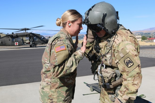 Illinois Army National Guard Sgt. Jessica Shelton of the 1844th Transportation Company, 108th Sutsainment Brigade talks with a UH-60 Blackhawk crew member from the U.S. Army's 16th Combat Aviation Brigade during medevac training as part of Rising Thunder 2019 at Yakima Training Center in Yakima, Washington, August 30, 2019. Rising Thunder 2019 is an annual exercise between the U.S. Army and the Japan Ground Self-Defense Force (JGSDF) and is part of Pacific Pathways 19-3. RT19 is a USARPAC-sponsored capstone event. U.S. Army Units participating include the 7th Infantry Division and the Illinois Army National Guard's 108th Sustainment Brigade and 33rd Infantry Brigade Combat Team. The exercise consists of company/platoon unilateral and bilateral training events in two phases, culminating with a bilateral live-fire exercise. (U.S. Army photo by Spc. Shaylin Quaid)