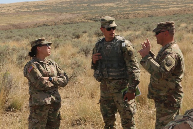 2nd Lt. Jamie Gunning (left), Capt. Theodore Tebbe (center), and Sgt. 1st Class Gary Cunningham (right), all from the Illinois Army National Guard's 1844th Transportation Company, conduct an after action review following IED lane training as part of Rising Thunder 2019 at Yakima Training Center in Yakima, Washington, August 30, 2019. Rising Thunder 2019 is an annual exercise between the U.S. Army and the Japan Ground Self-Defense Force (JGSDF) and is part of Pacific Pathways 19-3. RT19 is a USARPAC-sponsored capstone event. U.S. Army Units participating include the 7th Infantry Division and the Illinois Army National Guard's 108th Sustainment Brigade and 33rd Infantry Brigade Combat Team. The exercise consists of company/platoon unilateral and bilateral training events in two phases, culminating with a bilateral live-fire exercise. (U.S. Army photo by Spc. Shaylin Quaid)