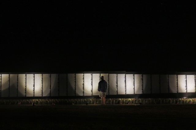 A man views the The Moving Wall, which is available to the public at all hours with the help of solar lights while displayed on Sackets Harbor Battlefield, August 24, in Sackets Harbor, New York. Volunteers from the Association of the United States Army coordinated the three day event for veterans, Soldiers and members of the community to experience the traveling half size replica of the Vietnam Veterans Memorial Wall in the North Country. Soldiers of the 41st Engineer Battalion, 2nd Brigade Combat Team, 10th Mountain Division helped assemble the wall, will provide security and be available to assist visitors around the clock while The Moving Wall is on display in the battalion's partnered community. (U.S. Army photo by Staff Sgt. Paige Behringer)