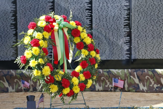 A memorial wreath for Spc. John Fuller, presented by Fuller's son, John Hoffman, sits at the base of The Moving Wall display, a traveling half size replica of the Vietnam Veterans Memorial Wall, following a memorial ceremony, August 24, in Sackets Harbor, New York. Maj. Gen. Brian Mennes, 10th Mountain Division commander, retired Col. Michael Plummer, former 10th MTN DIV chief of staff, accompanied Hoffman during the ceremont hosted by Volunteers from the Association of the United States Army and American Legion Post 1757. Retired Navy Capt. Father Joseph Sesito, a veteran of the Vietnam War, gave the invocation and benediction. Michelle Capone, Northern New York Fort Drum AUSA president, Molly Reilly, mayor of Sackets Harbor, Mennes and Plummer also spoke during the ceremony. John Condino and Vernon Datoush, both Vietnam veterans, read the 61 names of service members from the North Country who are memorialized on the Wall. AUSA volunteers coordinated The Moving Wall's visit for veterans, Soldiers and members of the community to experience the monument here in the North Country. Soldiers of the 41st Engineer Battalion, 2nd Brigade Combat Team, 10th MTN DIV helped assemble the wall, will provide security and be available to assist visitors around the clock while The Moving Wall is on display in the battalion's partnered community. (U.S. Army photo by Staff Sgt. Paige Behringer)