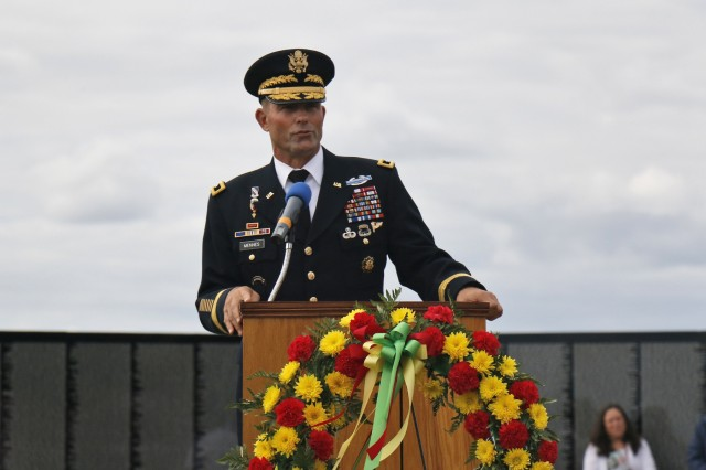 Maj. Gen. Brian Mennes, 10th Mountain Division commander, gives remarks during a memorial ceremony hosted by volunteers from the Association of the United States Army and American Legion Post 1757 in front of The Moving Wall display, a traveling half size replica of the Vietnam Veterans Memorial Wall, August 24, in Sackets Harbor, New York. Retired Navy Capt. Father Joseph Sesito, a veteran of the Vietnam War, gave the invocation and benediction. Michelle Capone, Northern New York Fort Drum AUSA president, Molly Reilly, mayor of Sackets Harbor, and retired Col. Michael Plummer, former 10th MTN DIV chief of staff and Vietnam veteran, also spoke during the ceremony. Mennes and Plummer accompanied John Hoffman as he laid a memorial wreath for his father, Spc. John Fuller. John Condino and Vernon Datoush, both Vietnam veterans, read the 61 names of service members from the North Country who are memorialized on the Wall. AUSA volunteers coordinated The Moving Wall's visit for veterans, Soldiers and members of the community to experience the monument in here the North Country. Soldiers of the 41st Engineer Battalion, 2nd Brigade Combat Team, 10th MTN DIV helped assemble the wall, will provide security and be available to assist visitors around the clock while The Moving Wall is on display in the battalion's partnered community. (U.S. Army photo by Staff Sgt. Paige Behringer)