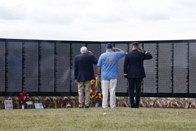 Maj. Gen. Brian Mennes, 10th Mountain Division commander, retired Col. Michael Plummer, former 10th MTN DIV chief of staff, and John Hoffman lay a memorial wreath for Hoffman's father, Spc. John Fuller, during a memorial ceremony in front of The Moving Wall display, a traveling half size replica of the Vietnam Veterans Memorial Wall, August 24, in Sackets Harbor, New York. Volunteers from the Association of the United States Army and American Legion Post 1757 hosted the ceremony on Sackets Harbor Battlefield. Retired Navy Capt. Father Joseph Sesito, a veteran of the Vietnam War, gave the invocation and benediction. Michelle Capone, Northern New York Fort Drum AUSA president, Molly Reilly, mayor of Sackets Harbor, Mennes and Plummer also spoke during the ceremony. John Condino and Vernon Datoush, both Vietnam veterans, read the 61 names of service members from the North Country who are memorialized on the Wall. AUSA volunteers coordinated The Moving Wall's visit for veterans, Soldiers and members of the community to experience the monument here in the North Country. Soldiers of the 41st Engineer Battalion, 2nd Brigade Combat Team, 10th MTN DIV helped assemble the wall, will provide security and be available to assist visitors around the clock while The Moving Wall is on display in the battalion's partnered community. (U.S. Army photo by Staff Sgt. Paige Behringer)
