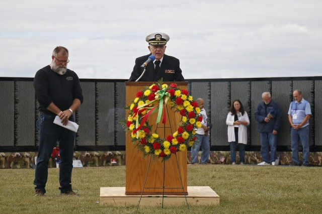 Retired Navy Capt. Father Joseph Sesito, a veteran of the Vietnam War, gives the invocation during a memorial ceremony hosted by volunteers from the Association of the United States Army and American Legion Post 1757 in front of The Moving Wall display, a traveling half size replica of the Vietnam Veterans Memorial Wall, August 24, in Sackets Harbor, New York. Michelle Capone, Northern New York Fort Drum AUSA president, Molly Reilly, mayor of Sackets Harbor, Maj. Gen. Brian Mennes, 10th Mountain Division commander, and retired Col. Michael Plummer, former 10th MTN DIV chief of staff and Vietnam veteran, also spoke during the ceremony. Mennes and Plummer accompanied John Hoffman as he laid a memorial wreath for his father, Spc. John Fuller. John Condino and Vernon Datoush, both Vietnam veterans, read the 61 names of service members from the North Country who are memorialized on the Wall. AUSA volunteers coordinated The Moving Wall's visit for veterans, Soldiers and members of the community to experience the monument here in the North Country. Soldiers of the 41st Engineer Battalion, 2nd Brigade Combat Team, 10th MTN DIV helped assemble the wall, will provide security and be available to assist visitors around the clock while The Moving Wall is on display in the battalion's partnered community. (U.S. Army photo by Staff Sgt. Paige Behringer)