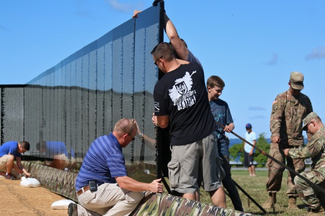 Volunteers from the Association of the United States Army and 41st Engineer Battalion unloaded and assembled The Moving Wall, a traveling half size replica of the Vietnam Veterans Memorial Wall, at the Sackets Harbor Battlefield, August 23, in Sackets Harbor, New York. Mountain Sapper Soldiers from 2nd Brigade Combat Team, 10th Mountain Division will provide security and be available to assist visitors around the clock while The Moving Wall is on display in the battalion's partnered community. AUSA volunteers coordinated The Moving Wall's visit for veterans, Soldiers and members of the community to experience a version of the monument here in the North Country. (U.S. Army photo by Staff Sgt. Paige Behringer)