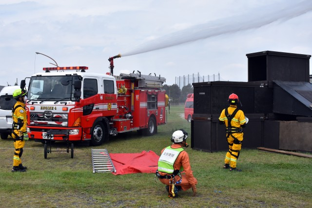 Firefighters with U.S. Army Garrison Japan Fire and Emergency Services assist their local counterparts during the Sagamihara City Disaster Drill on an area of returned land next to the U.S. Army Sagami General Depot, Sagamihara, Japan, Sept. 1.
