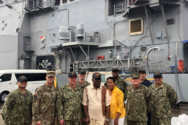Retired 1st Lt. Luther Manus and his wife, Connie, pose with a group of Sailors after touring the USS Chancellorsville—a Ticonderoga-class guided-missile cruiser—at Yokosuka Naval Base, Japan, Aug. 28. Manus was stationed at an ammunition depot near the base from 1947 to 1949.